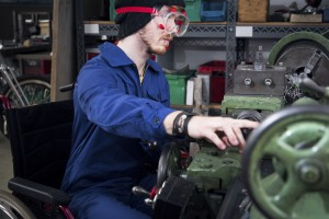 young mechanic / apprentice in wheelchair working on turning lathe